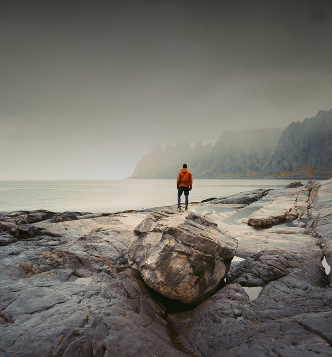 Adventurous man standing on stone. The Tungeneset rest area lie